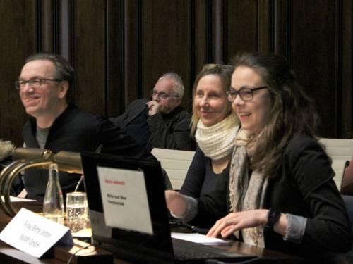 Vier Personen sitzen nebeneinander hinter Pulten im Hodlersaal des Neuen Rathauses und lachen.