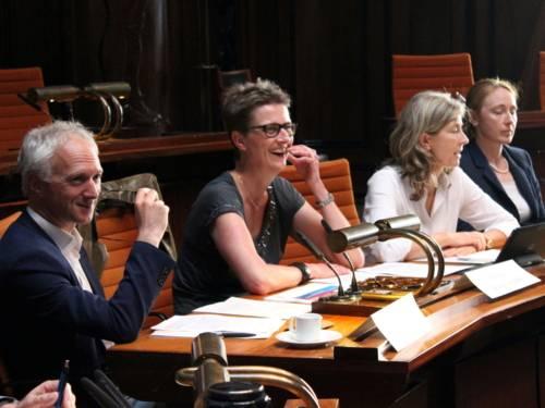 Vier Personen sitzen im Hodlersaal nebeneinander hinter Pulten. Der mann und die Frau, die links sitzen, blicken nach vorne und lachen.