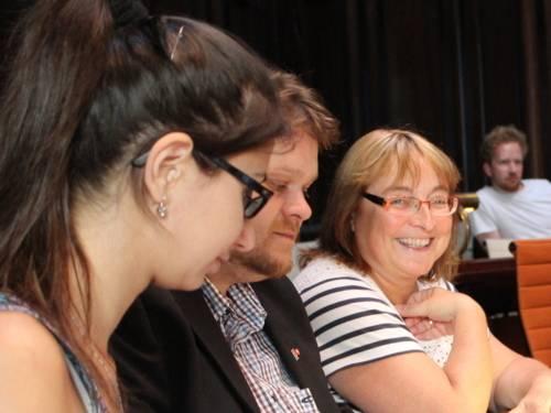 Drei Personen - zwei Frauen und ein Mann - sitzen nebeneinander im Hodlersaal hinter Pulten. Die hintere Frau lächelt.