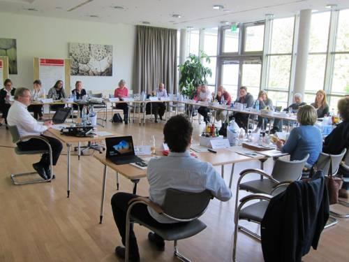 Etwa 25 Personen sitzen in einem Diskussionssaal hinter viereckig aufgestellten Tischen. Einige davon gestikulieren. Auf den Tischen liegen Papiere, Laptops und Getränke.