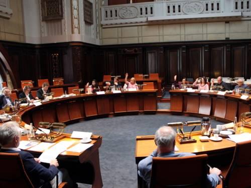 Etwa 12 Personen sitzen im Hodlersaal hinter Pulten. Einige davon heben die Hand zur Abstimmung hoch.