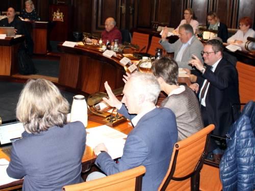 Etwa zehn Personen sitzen an kreisförmig aufgestellten Pulten im Hodlersaal des Neuen Rathauses. Drei davon heben den Arm zur Abstimmung.