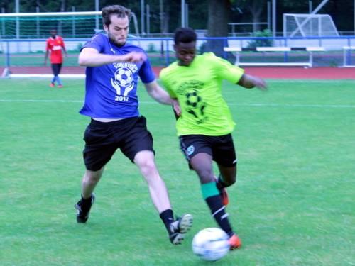 Zwei Männer mit verschiedenfarbigen Trikots kämpfen um einen Ball.