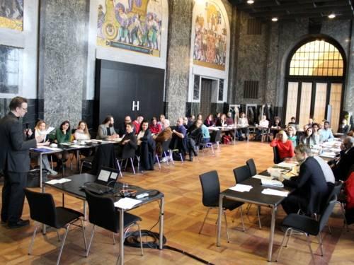 Etwa 70 Personen sitzen im Mosaiksaal des Neuen Rathauses an U-förmig aufgetellten Tischen. Links steht der Moderator und spricht in ein Mikrofon.
