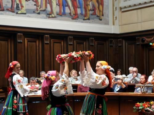 Zwei in Trachten gekleidete Frauen stehen in der Mitte des Hodlersaals des Neuen Rathauses und halten von zwei gegenüberliegenden Seiten einen Blumenkranz in ihrer Mitte. Links daneben tanzt eine weitere Frau in Tracht. Dahinter sitzen die Teilnehmer*innen der Veranstaltung.