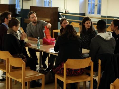 Acht Personen sitzen im Haus der Jugend an einem Tisch. Ein Mann greift in einen Stapel Moderationskarten, die in der Mitte des Tisches liegen.