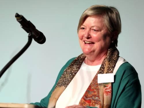 Eine Frau steht im Europasaal des Hauses der Jugend an einem Redner*innenpult und spricht.