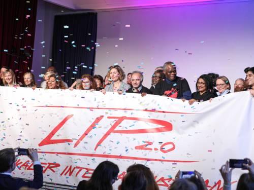 Circa 30 Menschen stehen auf einer violett beleuchteten Bühne, während im Vordergrund etliche Zuschauerinnen mit Handys fotografieren. Die Menschen in der ersten Reihe auf der Bühne halten ein großes Banner hoch, auf dem steht LIP 2.0 Lokaler Integrationsplan.