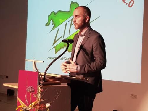 Ein Mann steht im Haus der Jugend auf einer Bühne hinter einem Rednerpult und spricht. Hinter ihm ist das LIP 2.0-Logo per Beamer an die Wand projiziert.