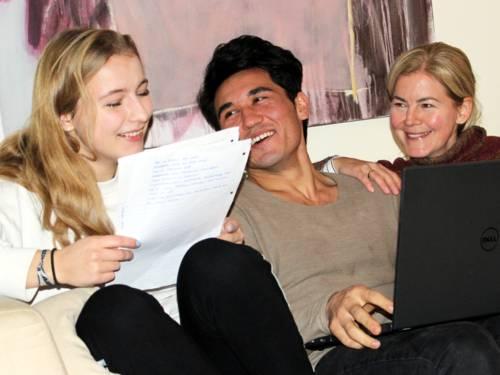 Zwei Jugendliche und eine Frau sitzen nebeneinander auf einem Sofa. Die Jugendliche links hält einen Stapel Papiere in der Hand, der Jugendliche in der Mitte hat einen laptop auf dem Schoß. Die Frau rechts im Bild blickt zum Jugendlichen in der Mitte. Alle drei lächeln.