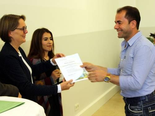 Eine Frau übergibt einem lächelndem Mann eine Urkunde. Hinter den beiden steht eine weitere Frau.
