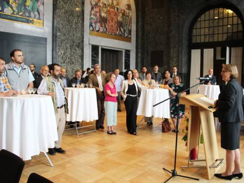 Eine Frau steht im Mosaiksaal des Neuen Rathauses vor einem Fenster an einem Stehpult und spricht in ein Mikrofon. Links im Bild stehen halbkreisförmig etwa 30 Personen an Stehtischen und blicken zur Rednerin.
