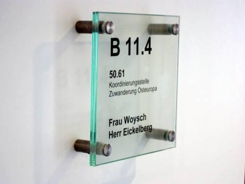 """Foto eines transparenten Büroschildes, auf dem steht """"Koordinierungsstelle Zuwanderung Osteuropa und die Namen """"Frau Woysch"""" und """"Herr Eickelberg""""."""