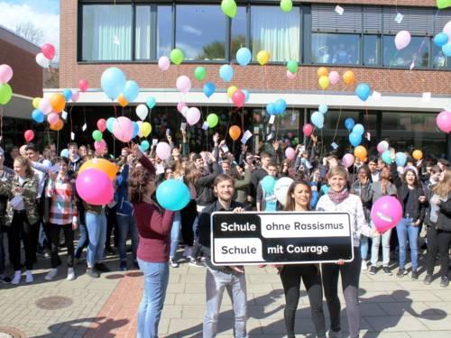 Etwa 80 Schüler/innen stehen hinter vier Lehrer/innen die das typische SOR-SMC-Banner vor sich halten. Die Schüler/innen lassen Ballons in den Himmel steigen, an denen Postkarten befestigt sind.
