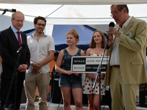 Fünf Personen stehen auf einer Bühne im Freien nebeneinander. Die rechte Person spricht in ein Mikrofon und schaut in Richtung der ganz links stehenden Person.