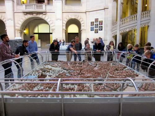 Am Stadtmodell in der Kuppelhalle des Neuen Rathauses stehen etwa 15 Jugendliche und schauen auf die Stelle, auf die der Referent mit seinem Stock zeigt. Manche schauen in ihre Unterlagen, oder machen Notizen.