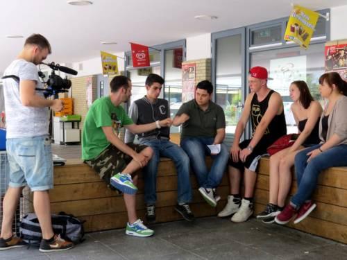 Sechs Schüler/innen und Spax sitzen auf einer Holzbank und sprechen miteinander. Links steht ein weiterer Schüler mit einer Videokamera und filmt.