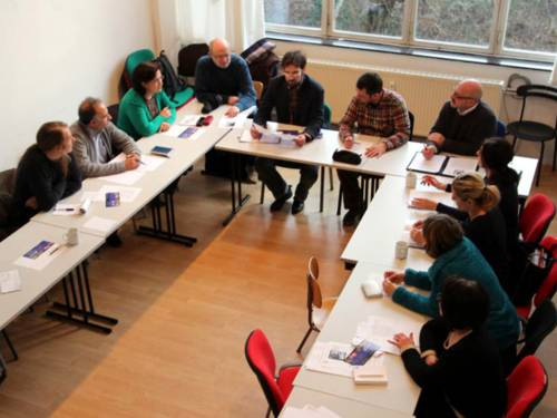 Etwa 13 Personen sitzen um einen U-förmigen Tisch und sprechen miteinander.