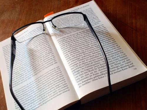 Foto von einem Buch, auf dem eine Brille liegt.