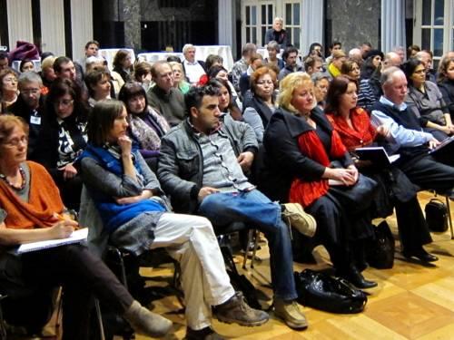 Etwa 60 Personen sitzen nebn- und hintereinander und schauen nach vorne.