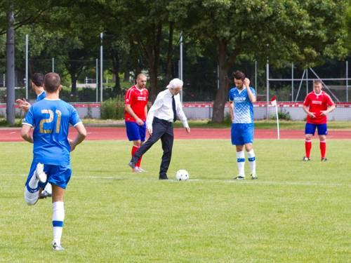 Ein Mann in Hemd und Anzughose führt einen Anstoß beim Fußball aus, um ihn herum Spieler in roten und blauen Trikots