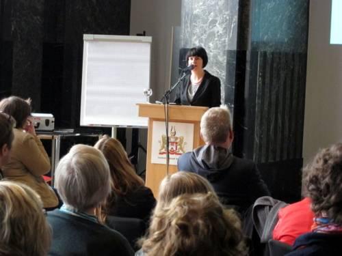 Eine Frau steht hinter einem Rednerpult und spricht. Vor ihr sind etwa 50 Zuschauer/innen von hinten erkennbar.