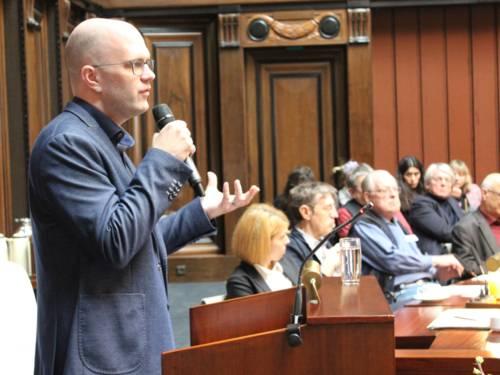 Ein Mann steht im Hodlersaal des Neuen Rathauses hinter einem Stehpult mit einem Mikrofon in der Hand und spricht. Rechts im Bild sind sitzende Zuhörer*innen erkennbar.
