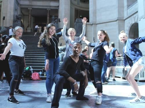 Fünf Mädchen und ein Mann posieren für die Kamera. Die Mädchen stehen und strecke die Arme aus, der Mann kniet in der Hocke.