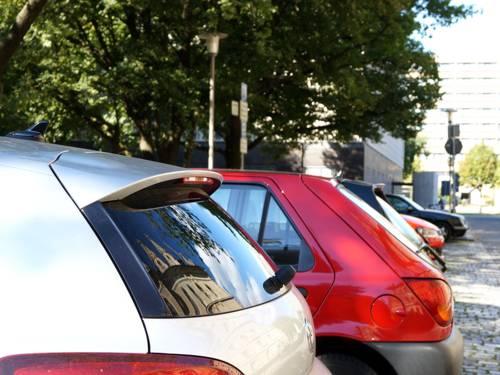Einige parkende Autos neben dem Neuen Rathaus