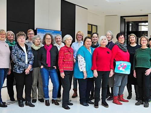 Gruppenfoto mit zwölf freundlich lächelnden Frauen unterschiedlichen Alters