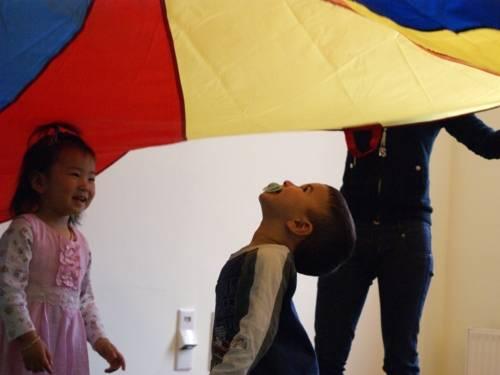 Kinder unter einem wehenden Tuch in einer Eltern-Kind-Gruppe