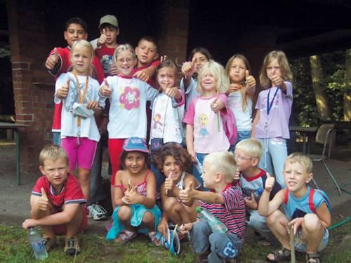 Eine Gruppe Kinder hält vor einem Familienzentrum die Daumen hoch