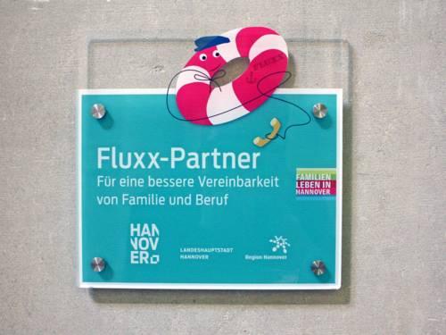 """Das Schild """"Fluxx-Partner"""" zeigt einen Rettungsring mit einem Telefonhörer und wird an Betriebe vergeben, die sich an der Notfall-Kinderbetreuung Fluxx beteiligen."""