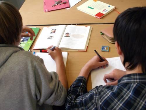 Über die Schultern von zwei Jugendlichen hinweg sind mehrere Schulbücher zu sehen, zudem schreiben die Jugendlichen gerade etwas in ihre Collegeblöcke