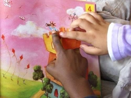 Kinderhände auf einem Bilderbuchmotiv