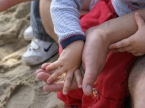 Ein Kind spielt mit dem Sand in den Händen seines Vaters.