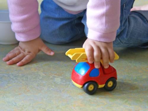 Ein Kleinkind spielt mit einem Spielzeugauto.