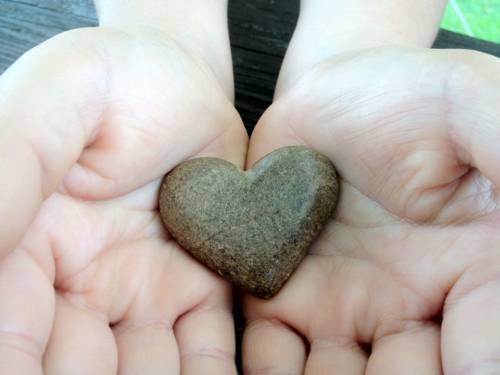 Stein in Herzform wird von zwei Händen getragen