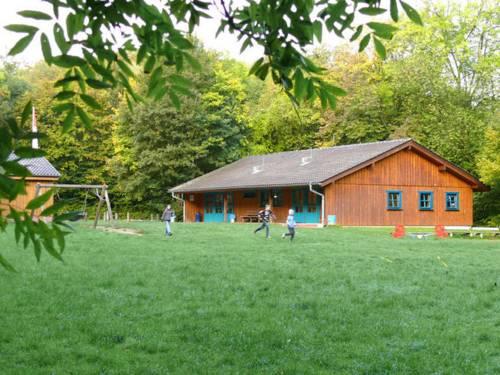 Holzhaus auf grüner Wiese mit spielenden Kindern