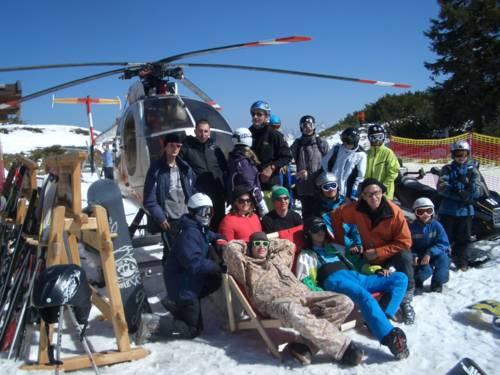 Jugendliche und Ihre Betreuer posieren im Schnee vor blauem Himmel und Helikopter