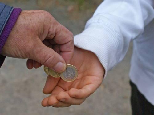 Aus einer älteren Hand erhält eine jüngere Hand Geldmünzen.