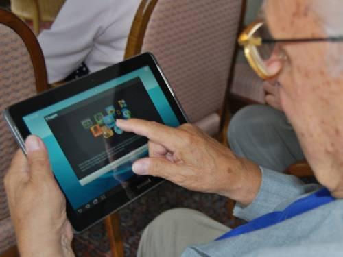 Ein älterer Herr verwendet einen Tablet-PC