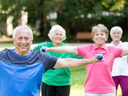 Drei ältere Frauen und ein älterer Herr in Sportkleidung bei der Gymnastik im Freien