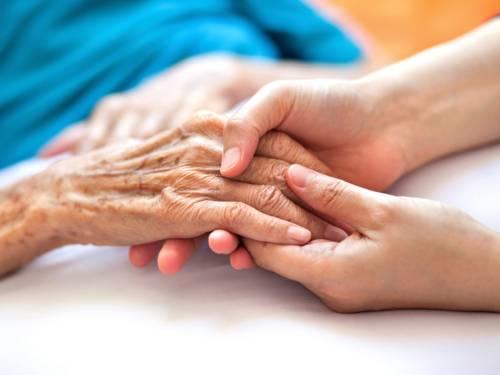 Eine Frau hält die Hand einer älteren Dame