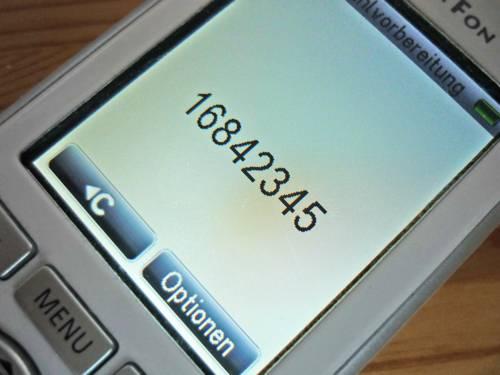 Auf dem Display eines Telefons ist die Nummer 168-42345 zu sehen.