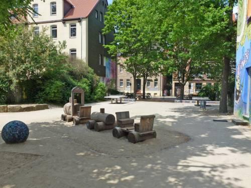 Auf dem Spielplatz in der Albertstraße sind unter Bäumen zwei Tischtennis-Platten zu sehen sowie eine Holzeisenbahn.