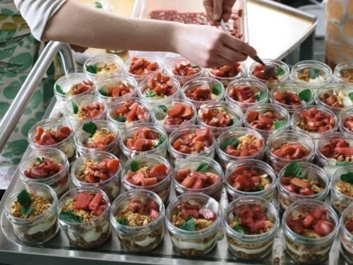 Viele Dessertportionen im Glas, die mit roten Früchten bedeckt sind
