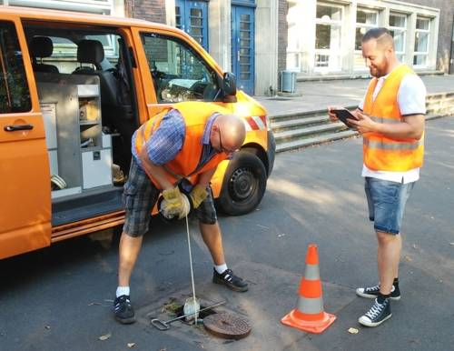 Zwei Mitarbeiter des Fachbereichs Umwelt und Stadtgrün in Warnwesten bei der Probennahme auf einer städtischen Fläche