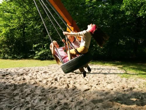 Zwei schaukelnde Kinder auf einem Spielplatz in Mühlenberg