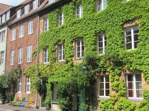 Mehrfamilienhaus am Ballhof mit begrünter Fassade und bunten Stühlen im Vordergrund